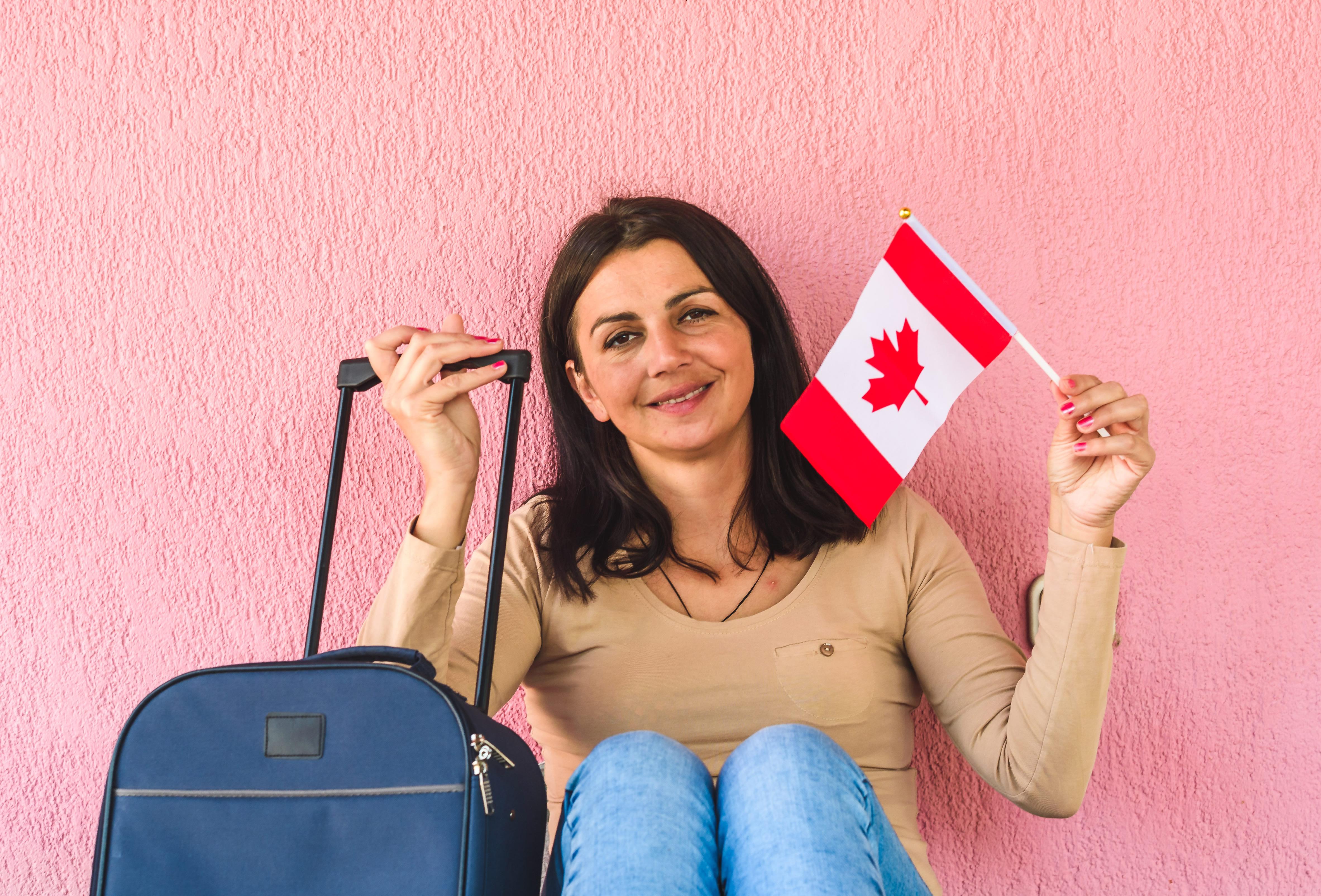 Женщина с флагом Канады, куда есть возможность переехать для беженцев