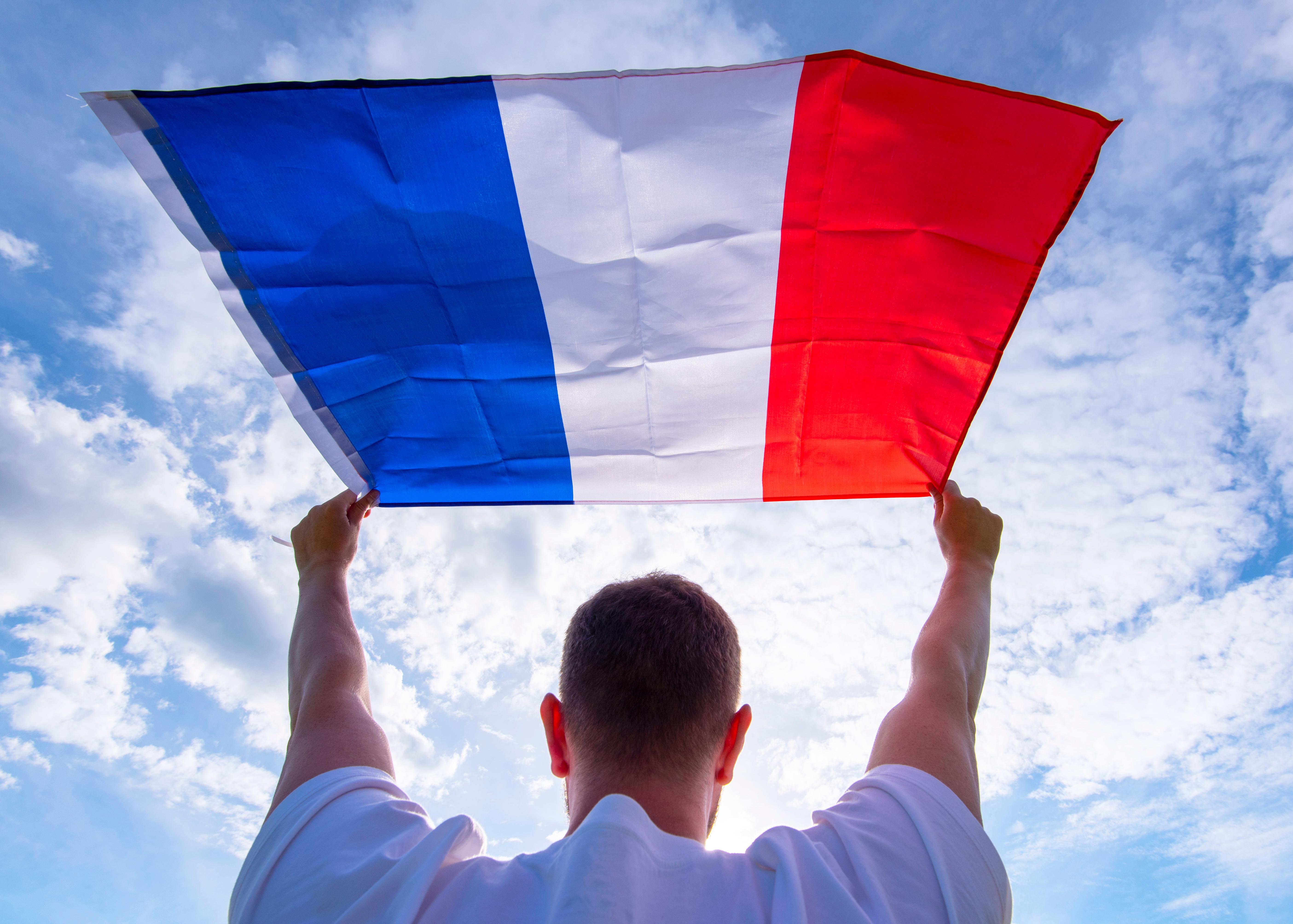 Мужчина с флагом Франции, куда есть возможность переехать для беженцев