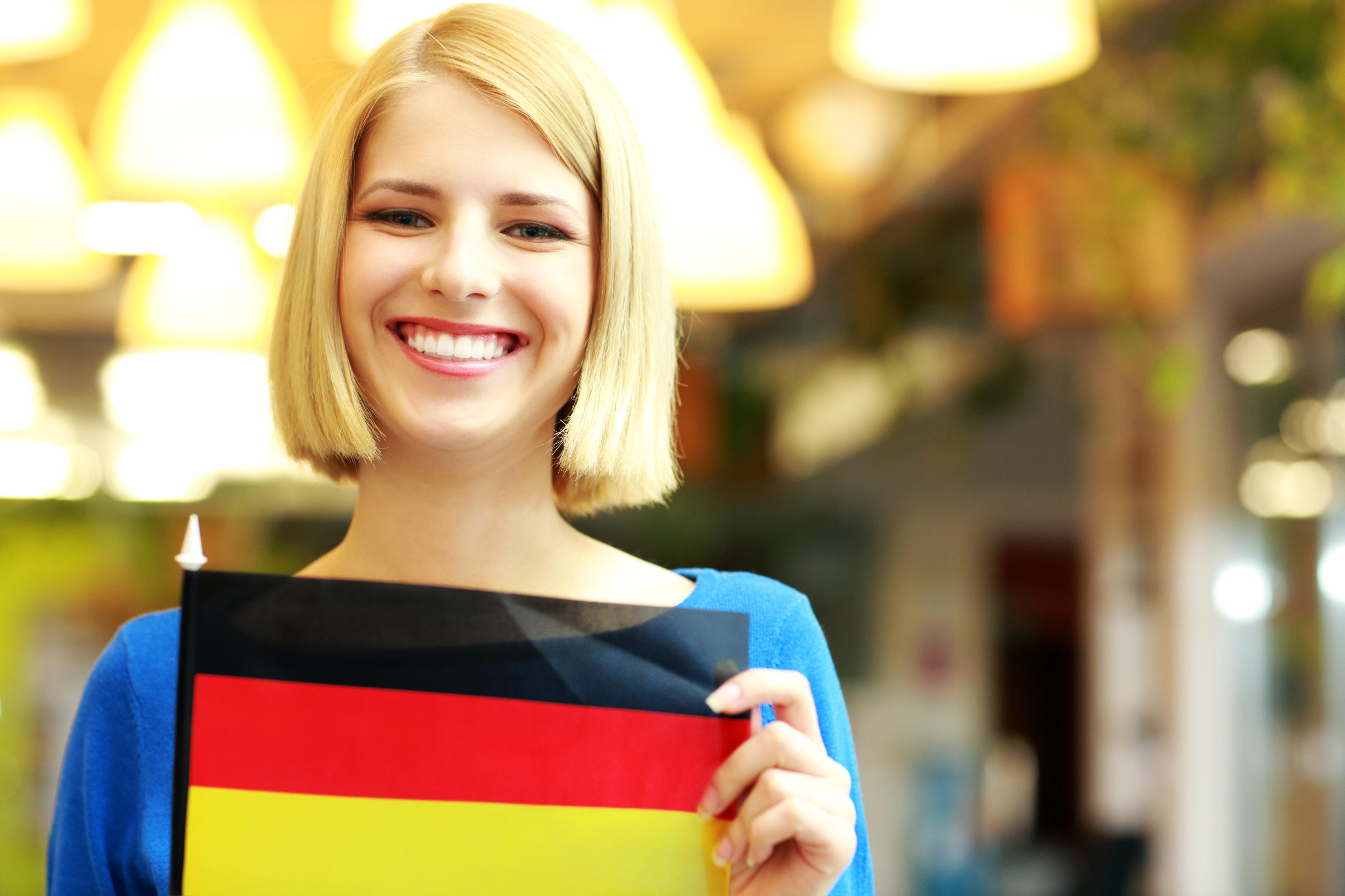 Девушка с флагом Германии, где студенческую визу могут оформить иностранцы