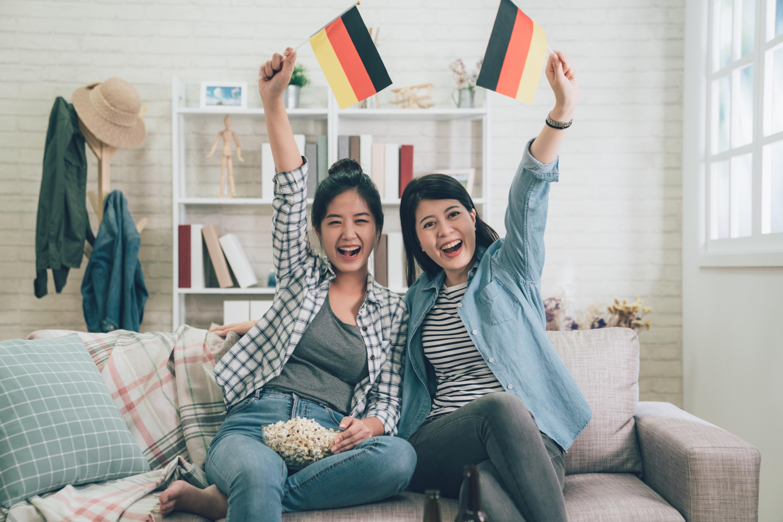 Девушки с флагами Германии, ПМЖ которой могут получить иностранцы