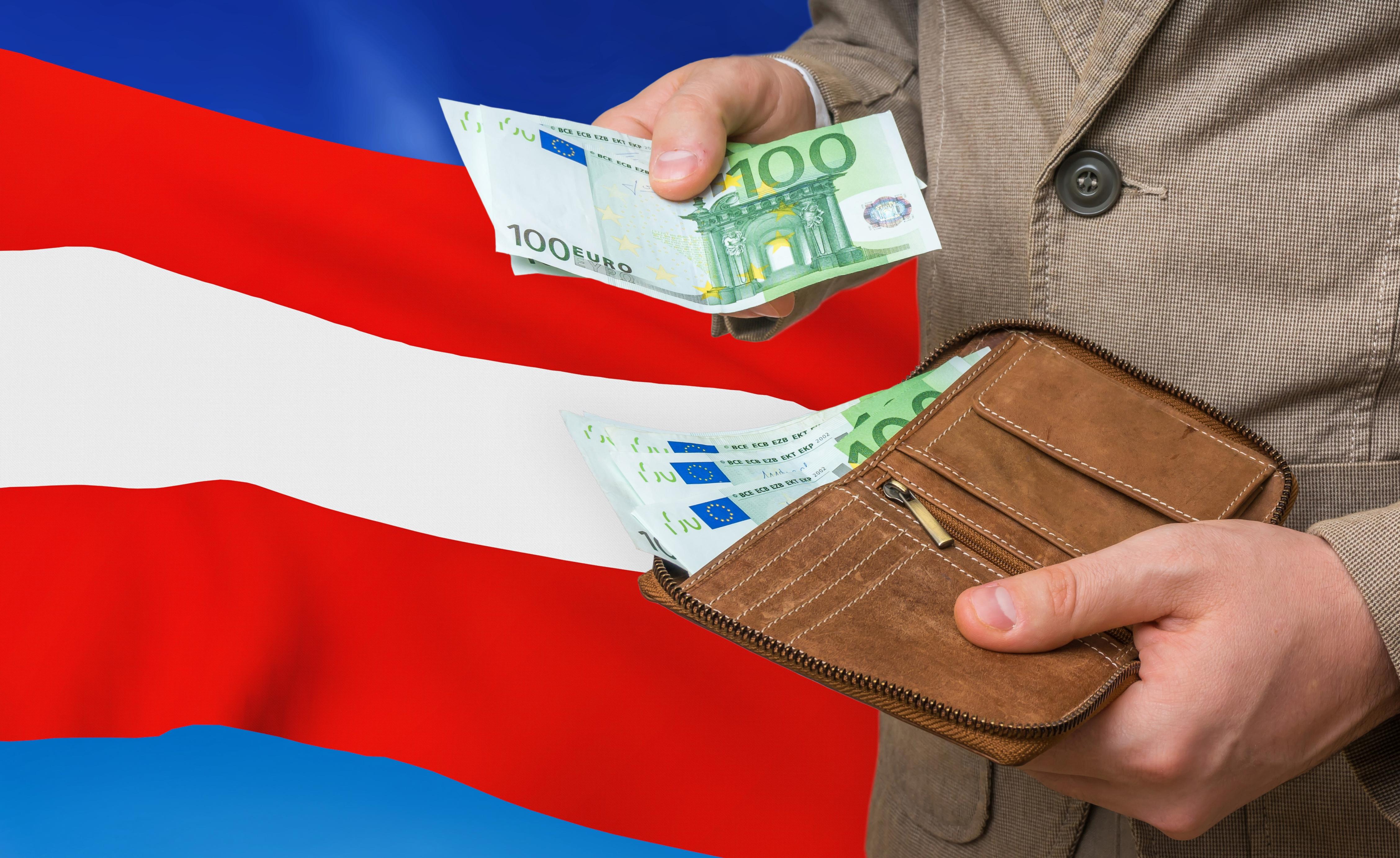 Деньги в руках мужчины на фоне флага Австрии, паспорт которой можно оформить за инвестиции