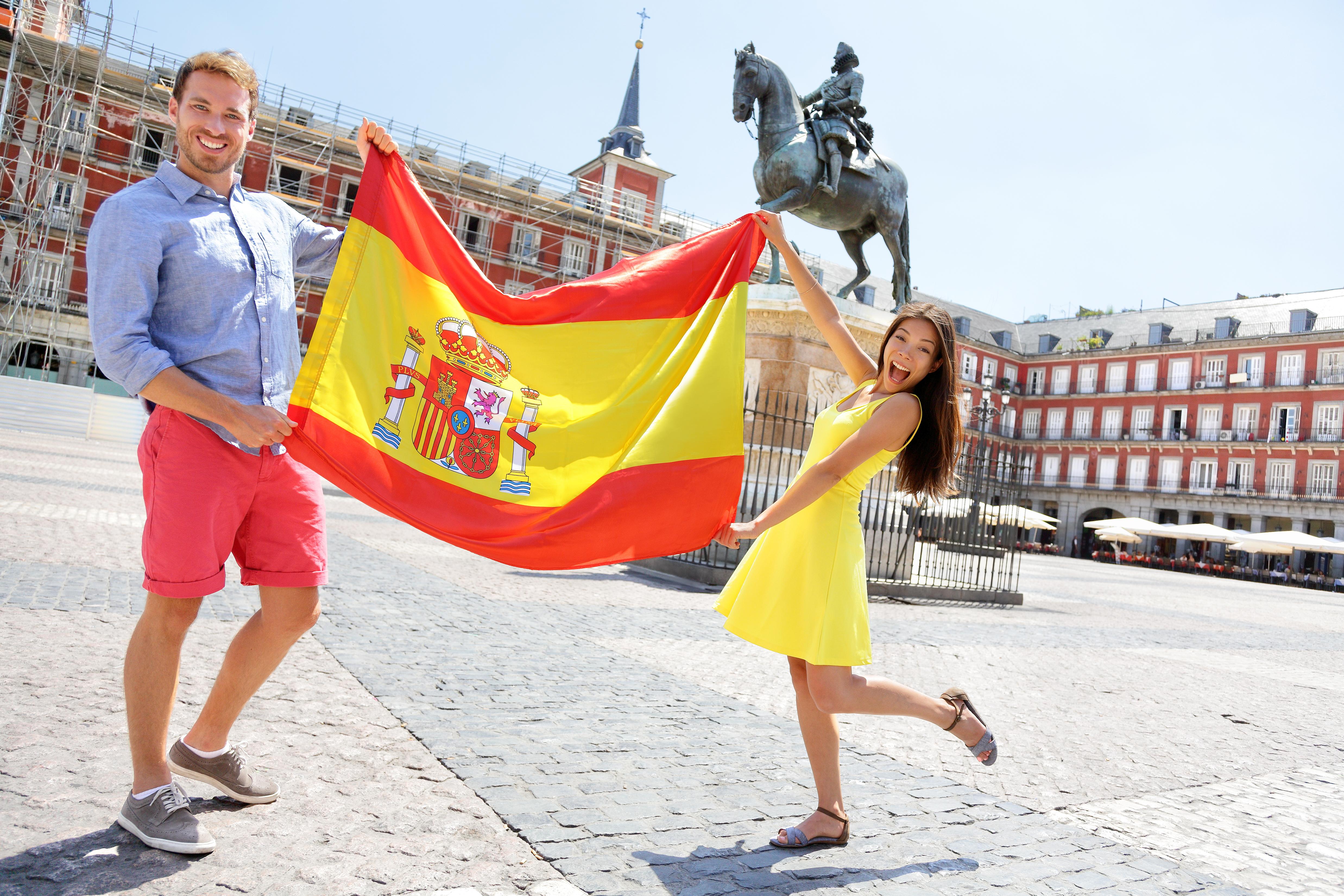 Молодые люди с флагом Испании, где студенческую визу могут оформить иностранцы