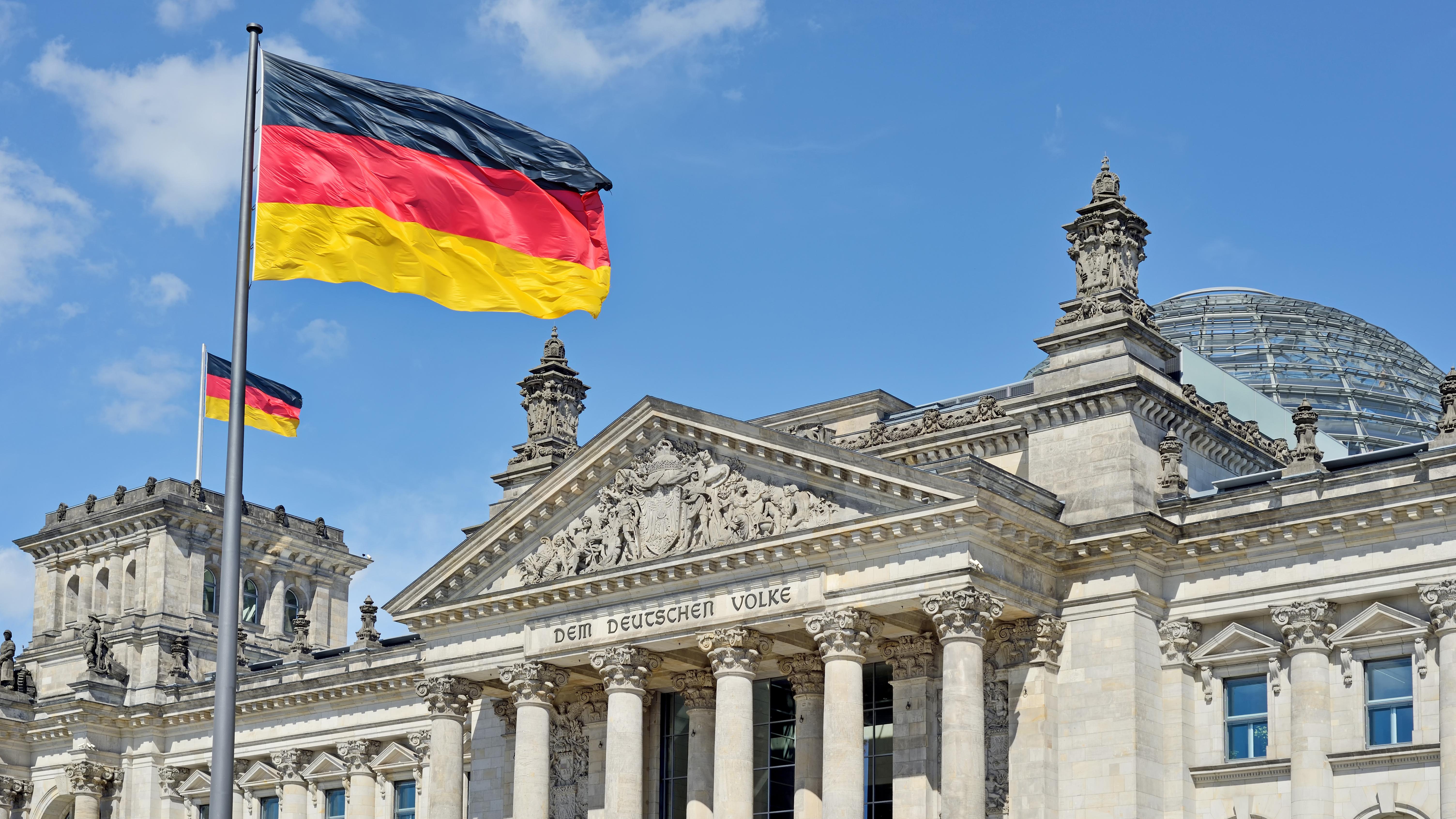 Немецкий флаг и здание парламента в Берлине, столице Германии, ПМЖ которой могут получить граждане России