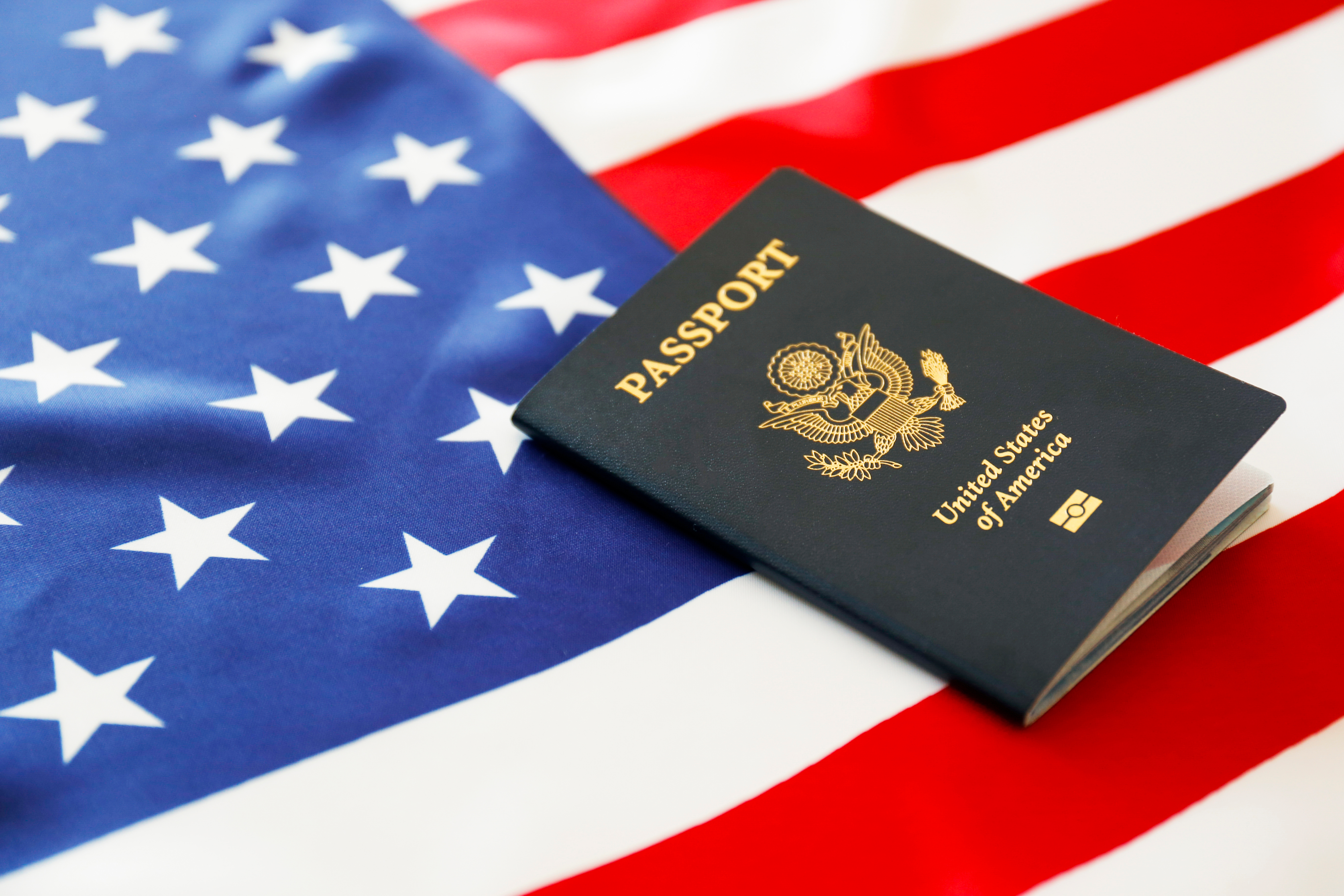 Флаг и паспорт США, гражданство которых можно получить
