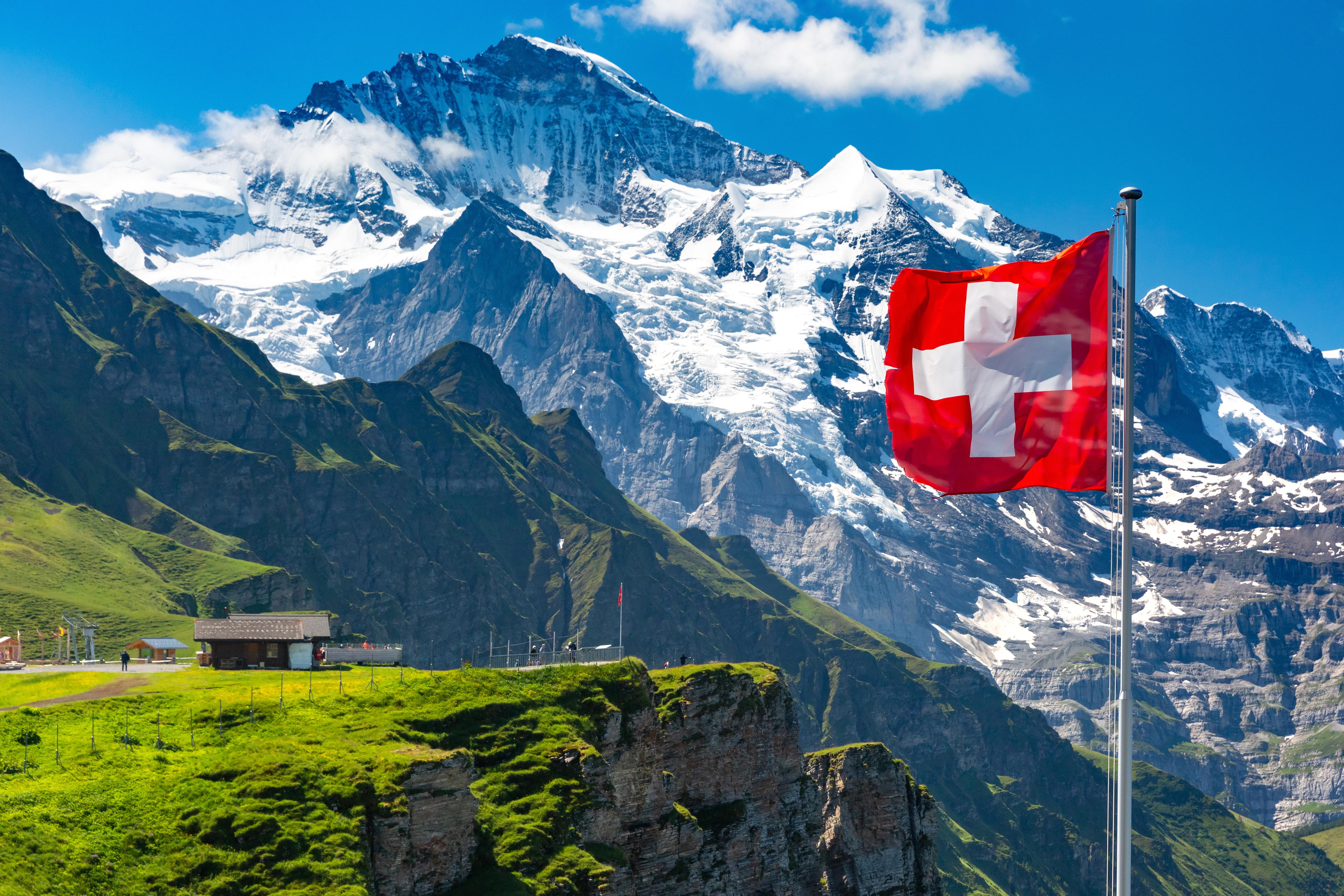 Флаг на фоне гор в Швейцарии, ПМЖ которой могут получить россияне, украинцы и белорусы