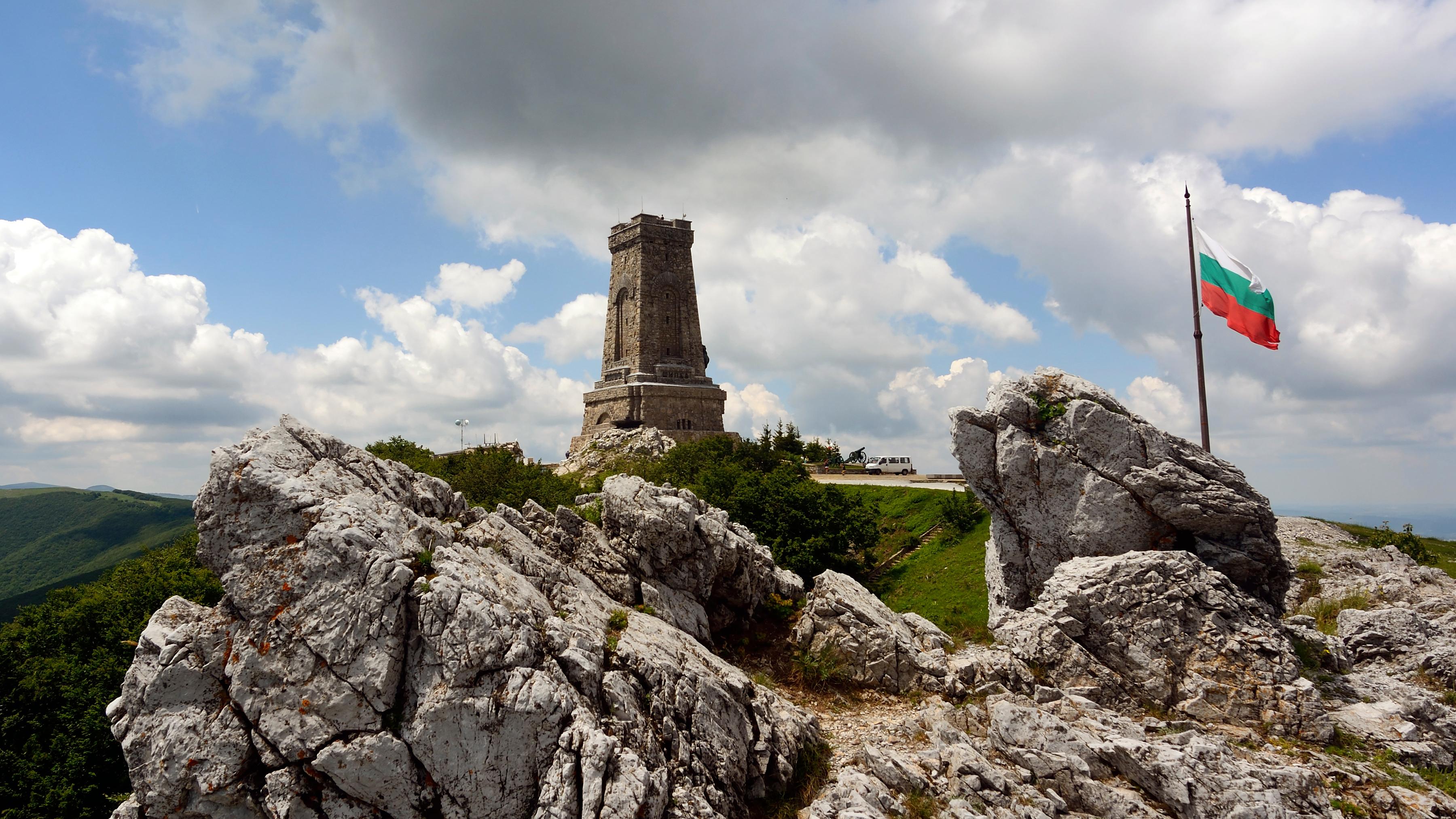 Флаг на фоне скалы в Болгарии, где можно получить ВНЖ