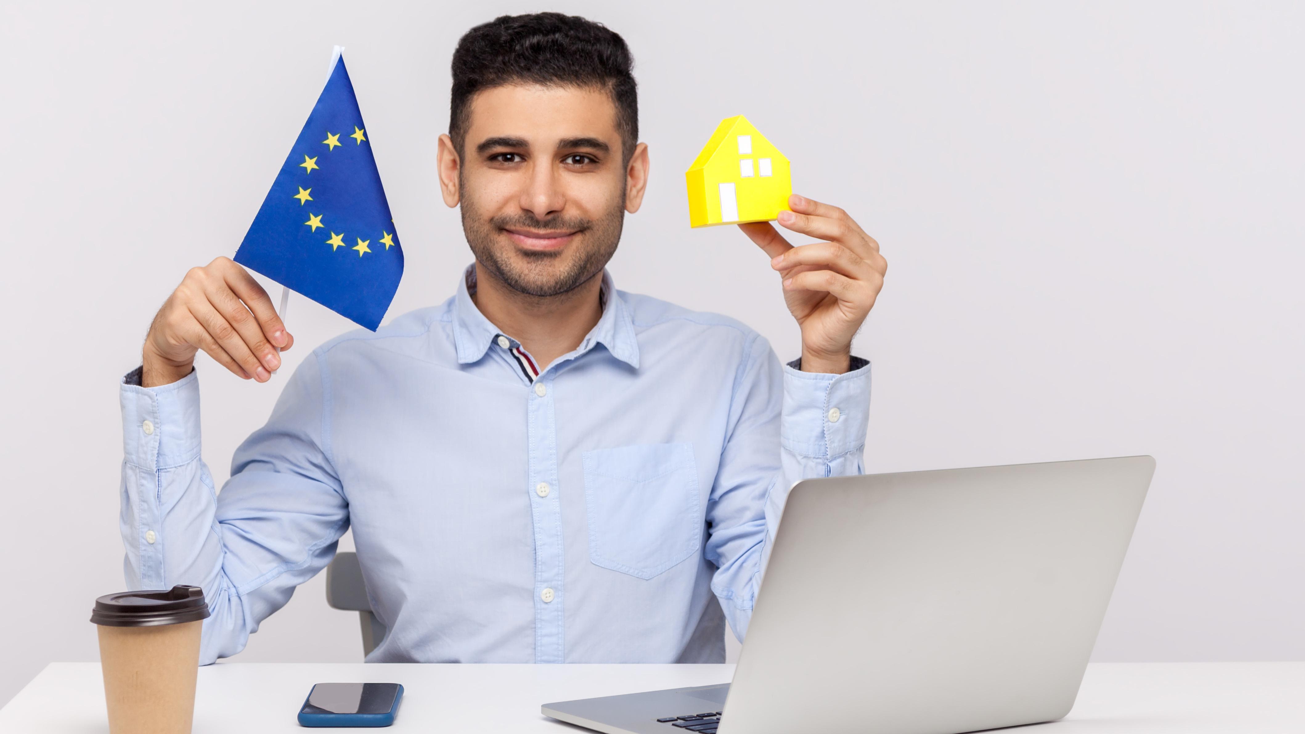 Мужчина держит флаг ЕС, где можно приобрести недвижимость