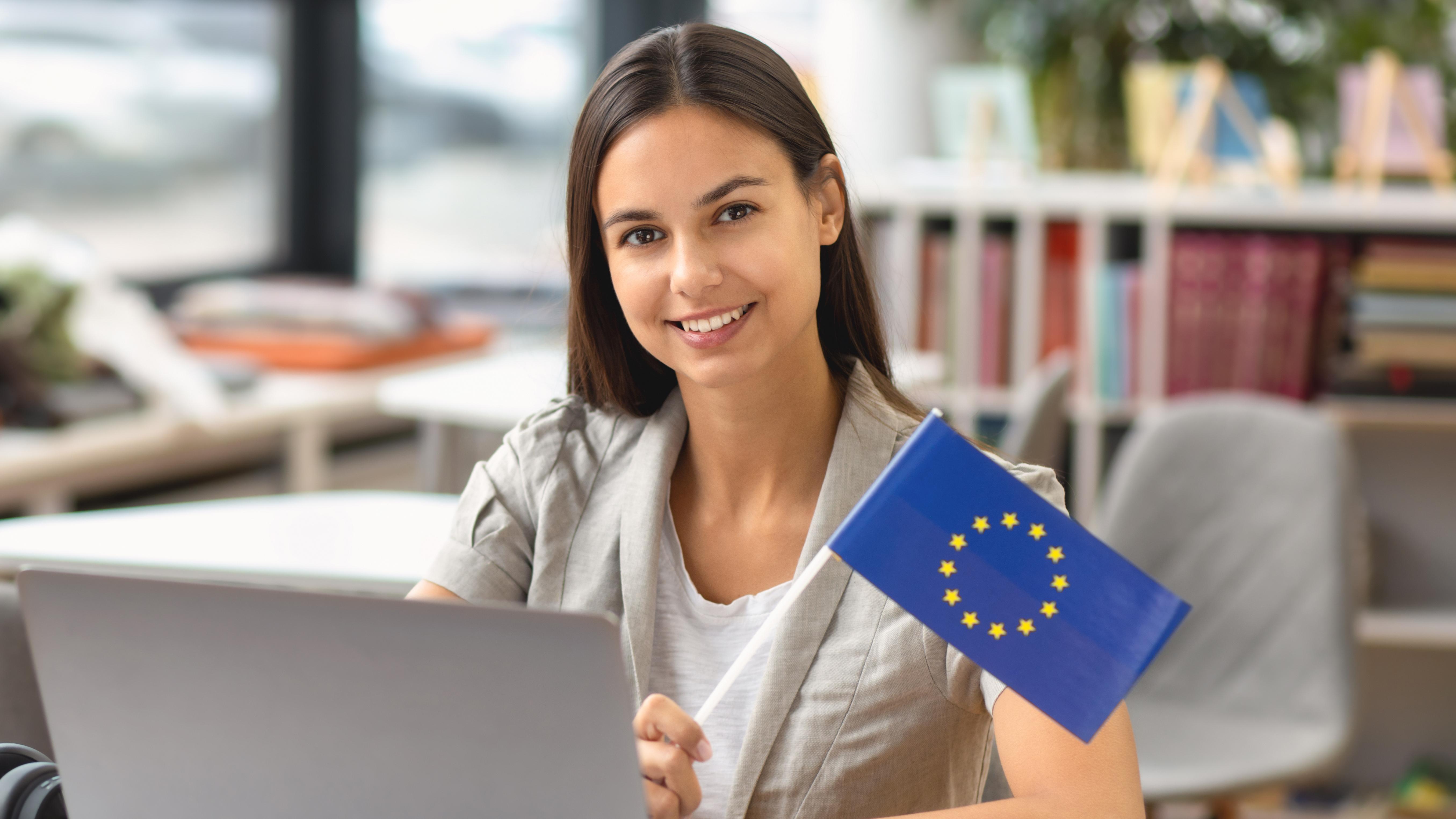 Девушка за компьютером с флагом ЕС, обучение в странах которого можно пройти