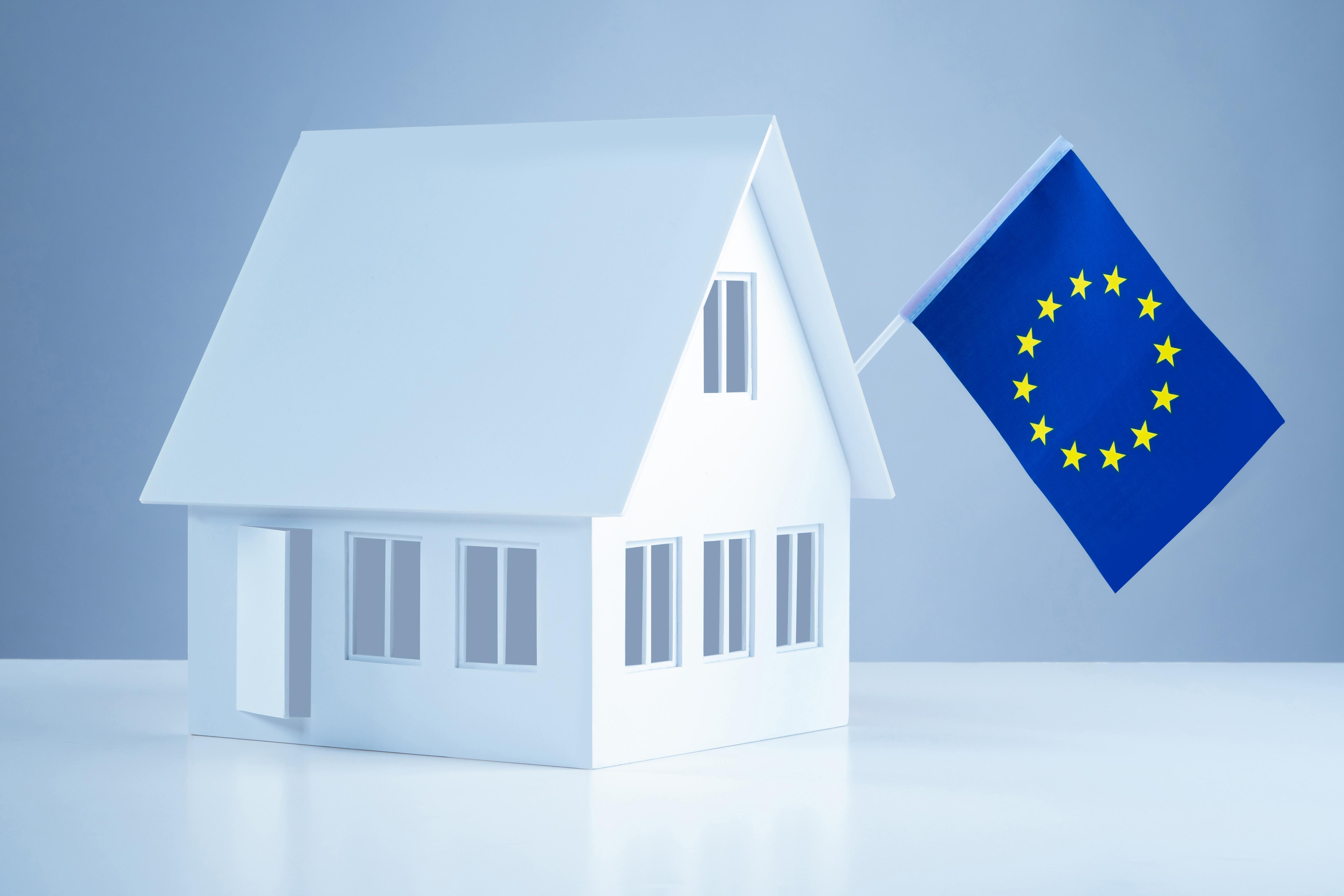 Дом и флаг ЕС, куда можно иммигрировать, купив недвижимость