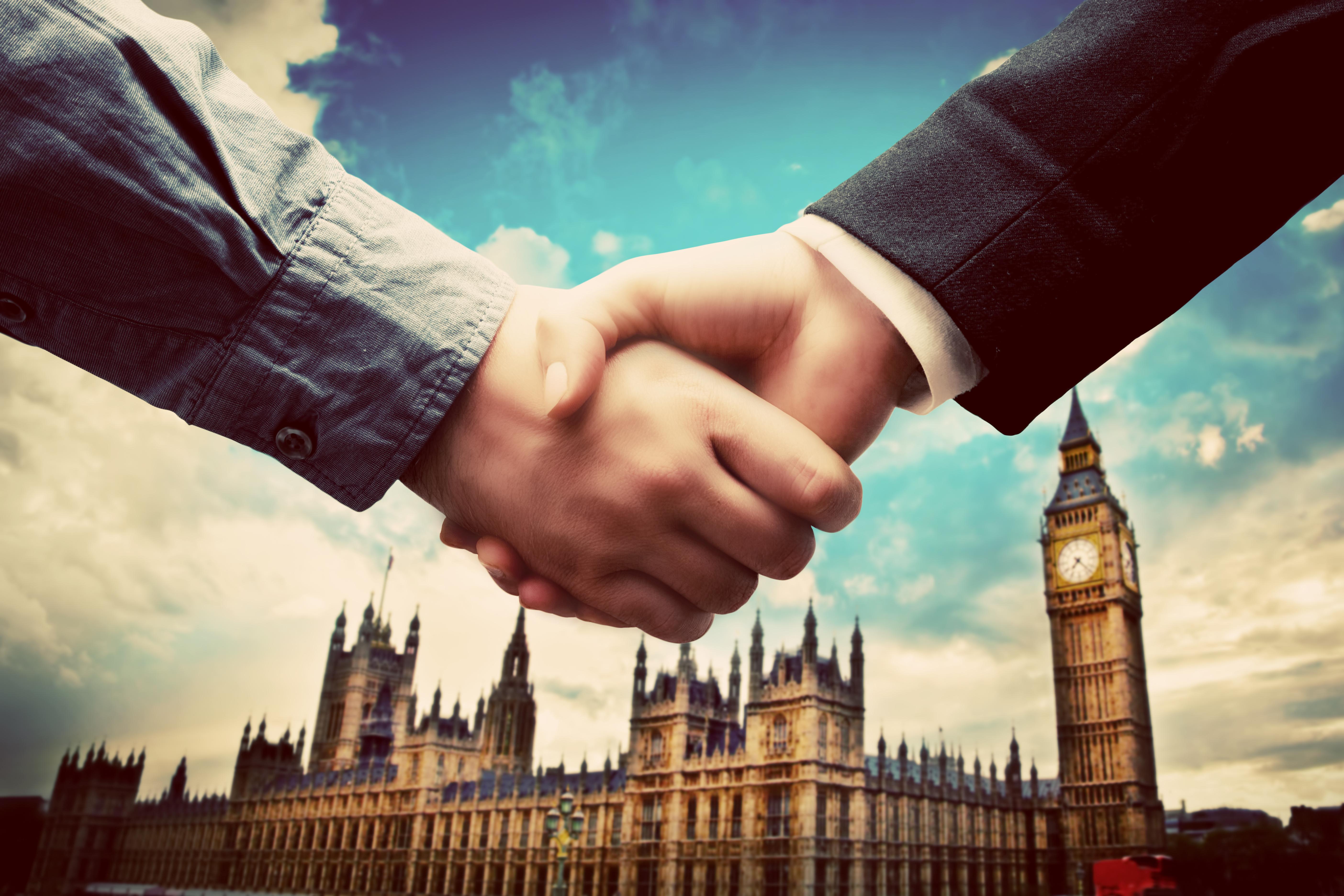 Рукопожатие на фоне Биг Бена в Англии, куда можно переехать по трудоустройству