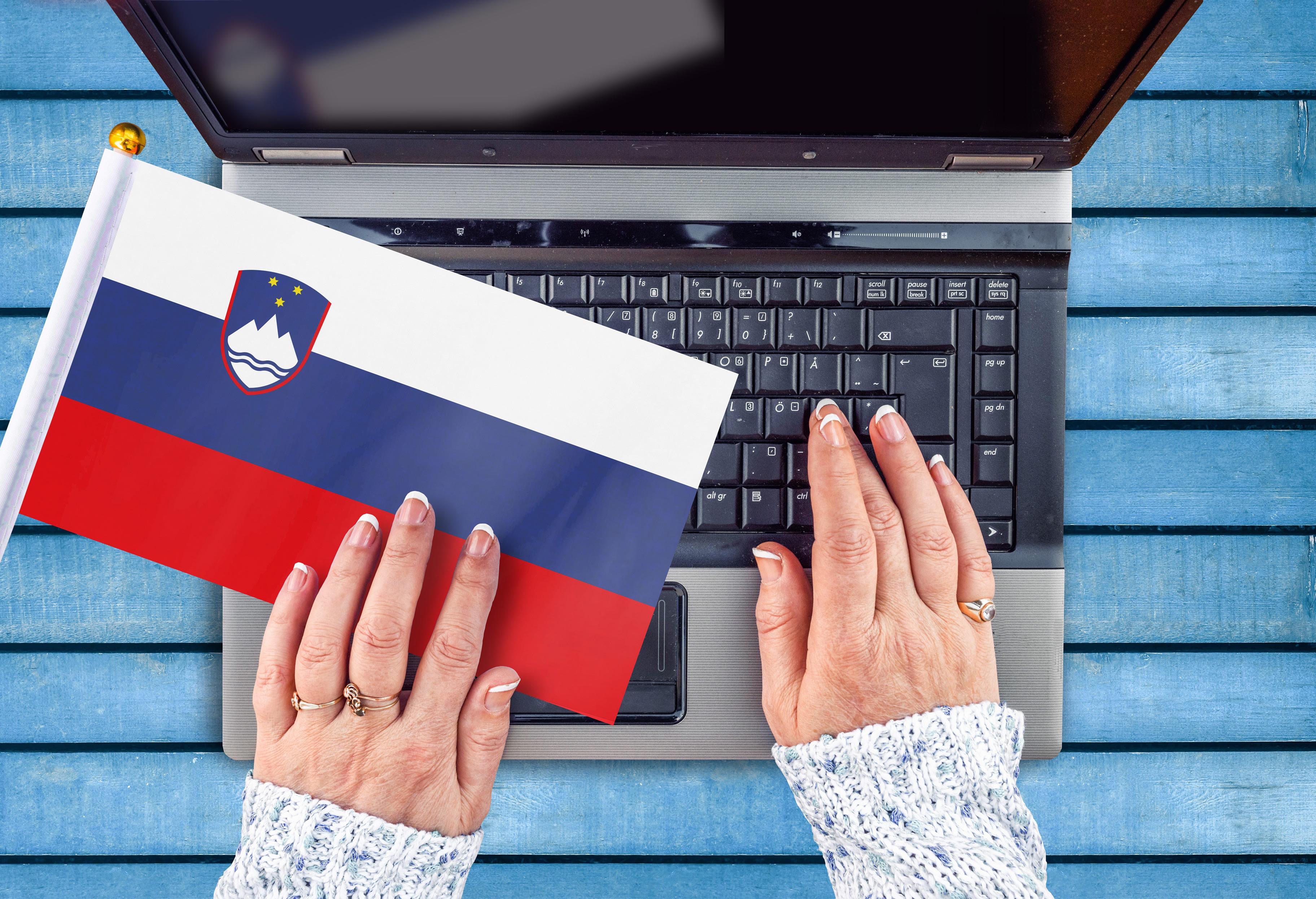 Женские руки, ноутбук и флаг Словении, работа в которой доступна для русских