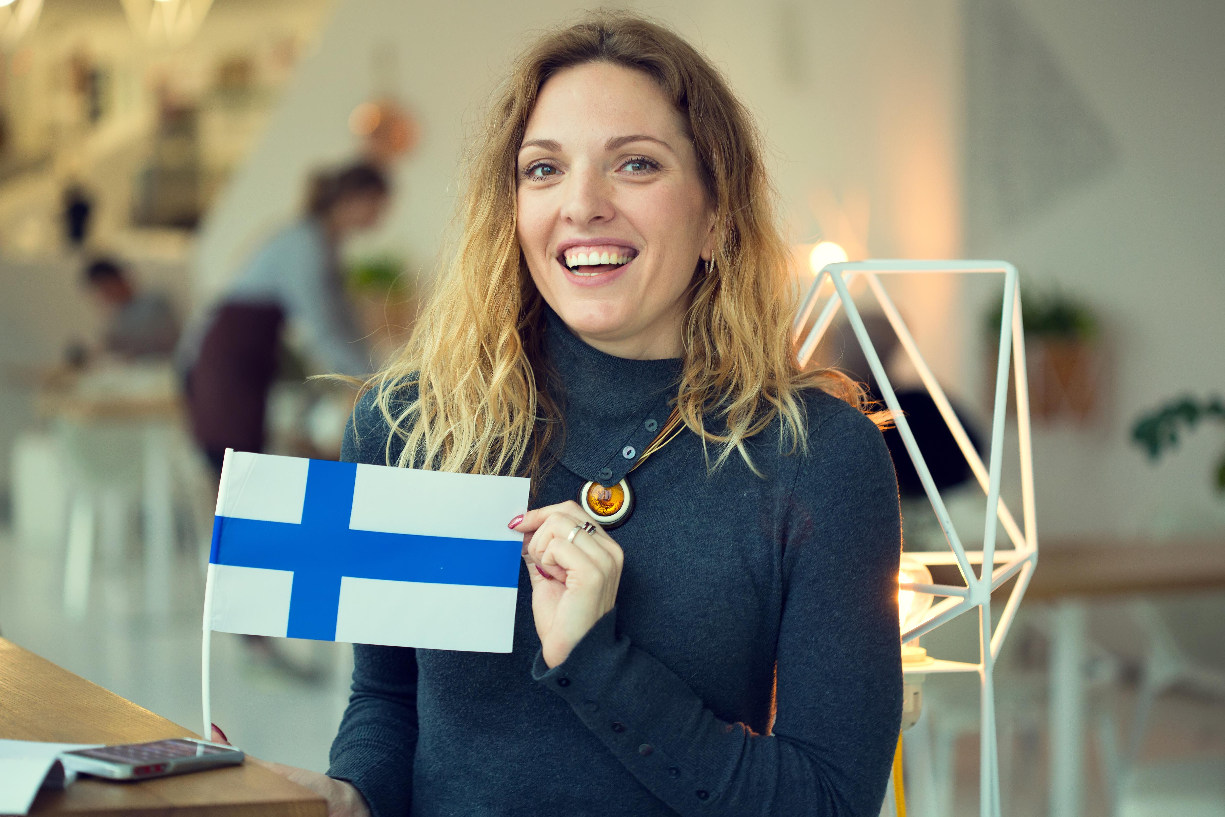 Студентка с флагом Финляндии, где существует условно-бесплатное образование для иностранцев