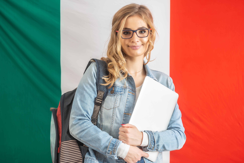 Девушка на фоне флага Италии, куда студенты могут получить визу
